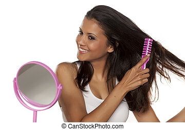 Young happy woman comb her long hair