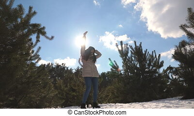 Young happy woman dances funny at the winter forest. Girl...