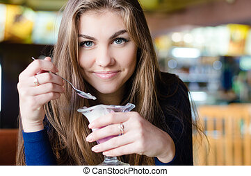 Young happy woman eating ice cream