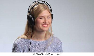 Young happy woman enjoying music with headphones.