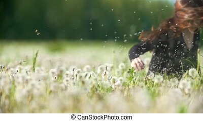 Young happy woman falling into a field of dandelions in sunny day