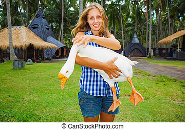 Young happy woman hold in hands funny pet - white goose