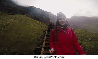 Young happy woman holding selfie stick with gopro and going...