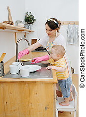 Young happy woman in a kitchen is washing her son toy car