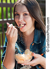 Young happy woman in cafe eating ice cream