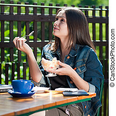 Young happy beautiful woman eating ice cream in cafe on open terrace