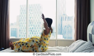 Young happy woman in dress falling down on bed, have fun at careless weekend time on the panoramic window background. Slow motion. 3840x2160