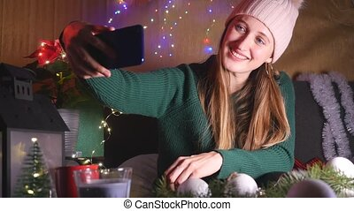 Young smiling woman in pink wool hat and green sweater take a selfie on Christmas background