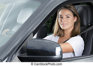 young happy woman in her new car