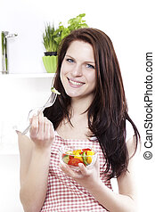 young happy woman in kitchen eating mixed salad
