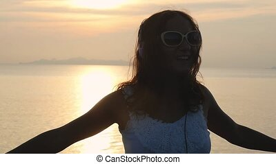 Young happy woman in sunglasses have fun listening to music in headphones at beautiful sunset with beautiful sea view. slow motion. 1920x1080