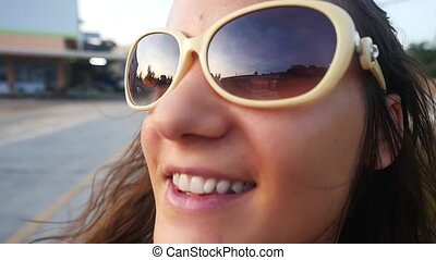 Young happy woman in sunglasses rides on motorbike on road...