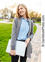 Young happy woman in the park with laptop on sunset background