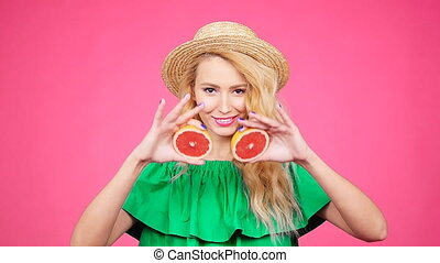 Young happy woman is holding slices of grapefruits to her eyes on pink background