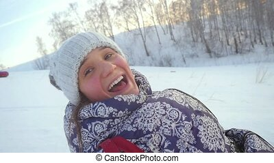 Young happy woman is sledding from the mountain through the snow in slow motion during beautiful sunset.