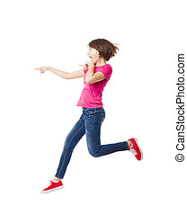 Young happy woman jumping and pointing