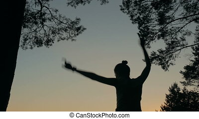 Young happy woman jumping, dancing and having fun in forest after sunset
