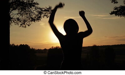 Young happy woman jumping, dancing and having fun in the forest at sunset