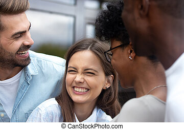 Young happy woman laughing at joke with friends close up