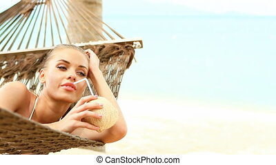 Young happy woman laying at hammock and drinking from ...