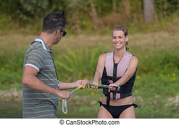 young happy woman learning water ski basics with coach