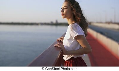 young happy woman looking at evening sunset on sea. pretty...