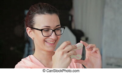 Young happy woman looking at photos on smartphone