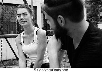 Young happy woman looking at young bearded man smiling and sitting on metal swings together in love at the old playground