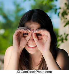 Young happy woman looking through finger goggles