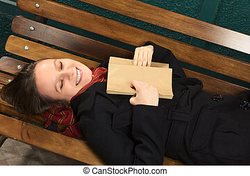 Young happy woman lying on a bench reading