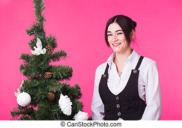 Young happy woman near christmas tree on pink background