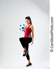 Young happy woman playing with soccer ball on gray background