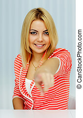 Young happy woman pointing at you