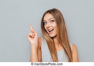 Young happy woman poiting finger up at copyspace isolated on...