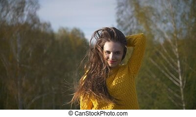 Young happy woman posing on the background of trees