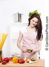 young happy woman preparing green paprika for salad