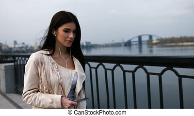 Young happy woman relaxing outdoors walking on a modern bridge while listening to music.