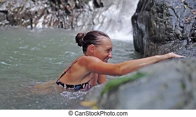 Young happy woman relaxing swimming in a pond in tropical waterfall. slow motion.