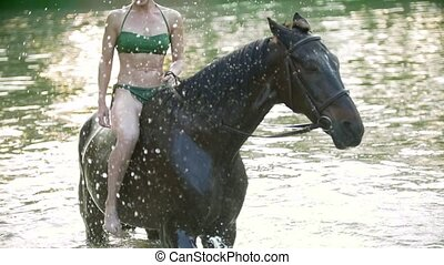 Young happy woman ride on black horse in the river at summer day