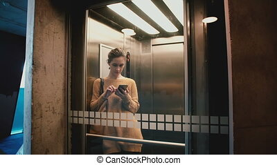 Young happy woman riding elevator with glass wall, door opens and she walks out using smartphone mobile shopping app.