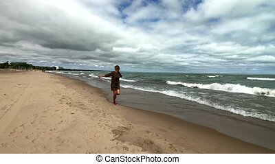 Young happy woman running on a beach
