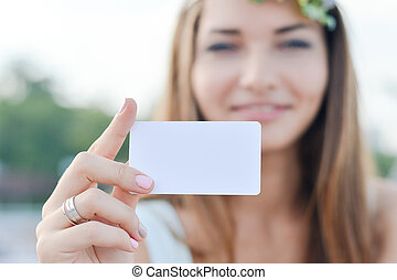 Young happy woman shows blank business card