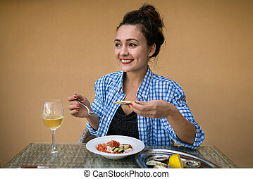 Young happy woman sits at the table with local food and glass