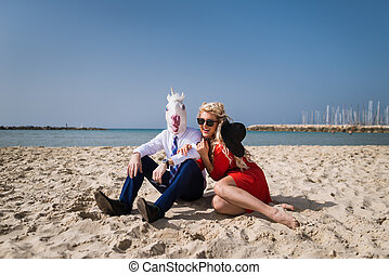 Young happy woman sits with businessman in funny mask