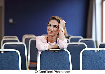 Young happy woman sitting alone in conference room
