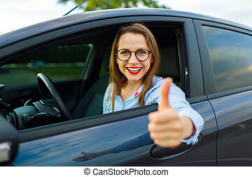 Young happy woman sitting in a car with thumb up