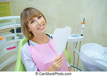 young happy woman sitting in the dentist's office, healthy teeth