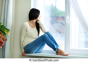 Young happy woman sitting on a window-sill and looking ...