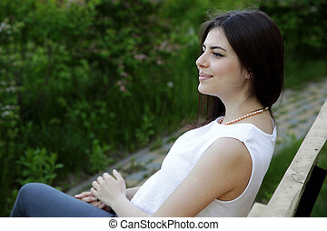 Young happy woman sitting on the bench in park
