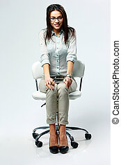Young happy woman sitting on the office chair on gray background